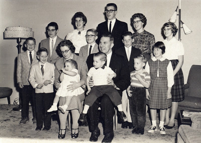 The entire Schlather clan, 1961: Seated, Virginia, holding Mary Agnes, not yet 1, and Bernie, holding Patrick, almost 2; Standing from the left are: Donald, 7, David, 4, William, 11, Margaret Ann, 14, Raymond, 10, Robert, 15, Paul, 9, Mary Rita, 17, Ken (in front), 3, Roseann, 6, and Jeanne Marie, 13.