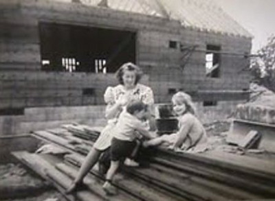 Virginia Schlather and her oldest children, Mary Rita and Bob, play on a pile of lumber as their house at 718 Gulf Road, Elyria, is under construction in the late 1940s.