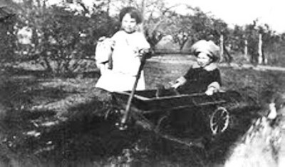 Little Bernie Schlather in the wagon and his sister, Ginny, in the early 1920s.