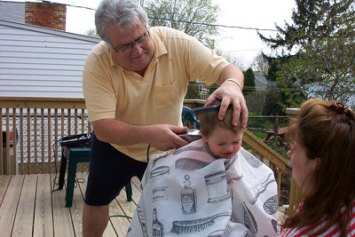 Tom Kuns made sure the heads of all of his grandkids were well-groomed. Here he is shown cutting his grandson Michael's hair.