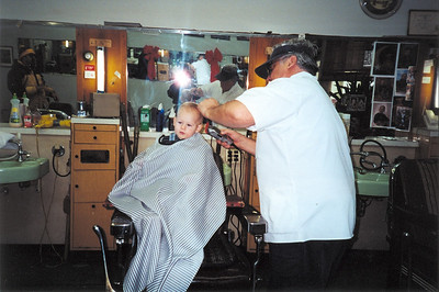 Tom Kuns gives his grandson Ryan his first haircut at Tom's Barber Shop in Lorain.