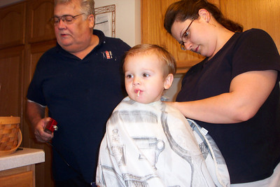 Tom Kuns has his clippers ready to give his grandson Will a haircut in the kitchen.
