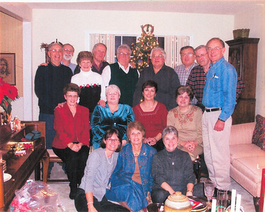 Tom Kuns, wearing black and white and standing next to the Christmas tree, is pictured with his siblings and their spouses.