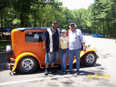 Tommie Jackson, right, son Jerome, left, and neighbor Linda Spizter, center, pose in June 2009 in front of a car that Tommie and Jerome restored.