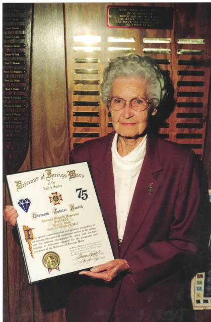 Velva Mihalis shows a plaque in 1998 honoring Thomas Mihalis VFW Post 1079 in Elyria on the 75th anniversary of its founding.