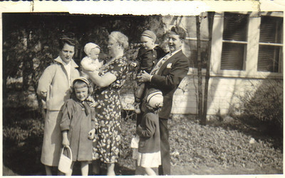 The Carrolls at Easter 1955 at Larry's mother's house: From left to right: Larry's neice Sheila with her hand on Marge's shoulder, baby Patrick being held by Larry's mother, Edna, and Maureen facing away from the camera to look at her little brother Michael who is being held by their father, Larry.