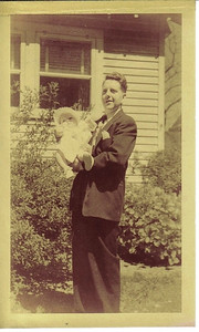 """Larry Carroll holds his firstborn child, Marjorie """"Marge,"""" in front of his parents' home in Cleveland in 1951."""
