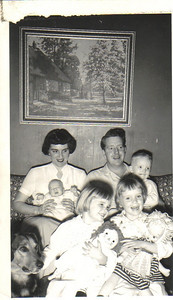 """Carroll family, 1954:  Back row, left to right, Mary Anne holding baby Patrick and Larry holding son Michael;  Front row, left to right, Maureen holding Raggedy Ann and Marge holding Dolly. Far left:. The family dog, aptly named """"'Plumber."""""""