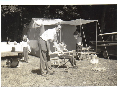 Larry Carroll pretends to be using an ax in front of his Sears-purchased Coleman tent at Maple Lakes Campground in Seville in 1963. Pictured from left to right are Plumber the dog, youngest son Tim, Larry the dad, Mike the eldest son seated in a lawn chair, middle son Patrick in the shade and the 1959 Buick Invicta station wagon that got them there.