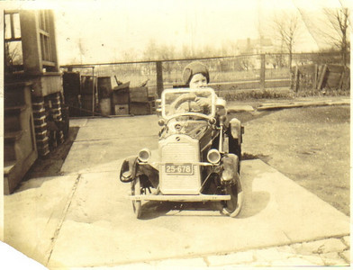 """Little Larry Carroll """"drives"""" a Packard replica on the concrete by the back door of his home on Rocky River Drive in Cleveland around 1929."""