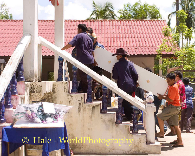 Friends Carrying Coffin Up Crematorium Stairway, Tahsang Village in Isaan region of Thailand