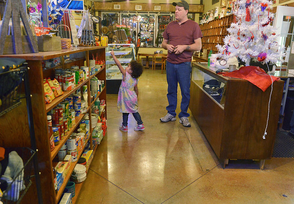 Globe/Roger Nomer<br /> Shaylee Evans, 4, points out a treat on the top shelf to her grandfather Robert Sullivan, Pittsburg, at Cowboy Bob's. The restaurant also features a fully stocked general store.
