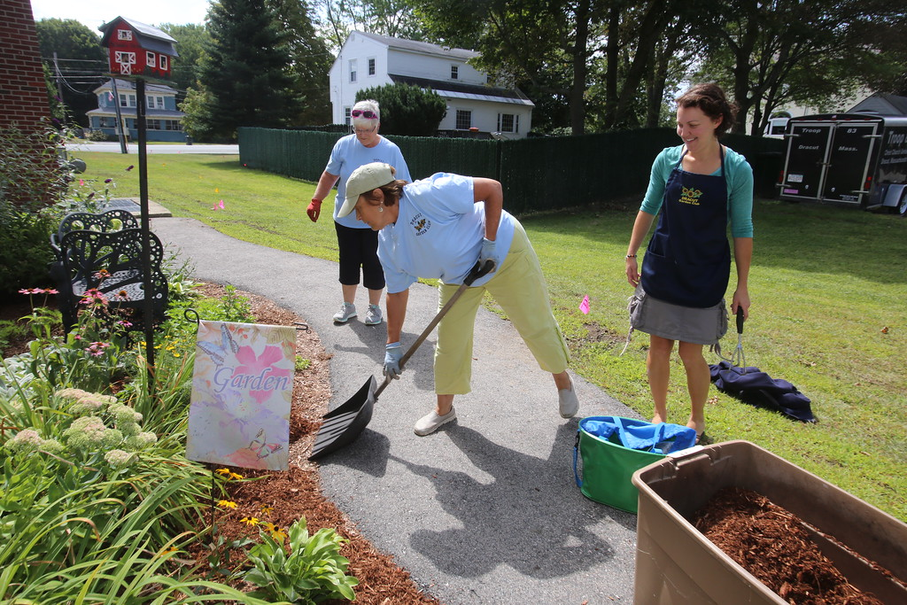 . Dracut Garden Club members Kathy Gauthier, Gail Morrissette and Leigh Cameron, at the beds the Garden Club put in at the Dracut Public Library. . (SUN/Julia Malakie)