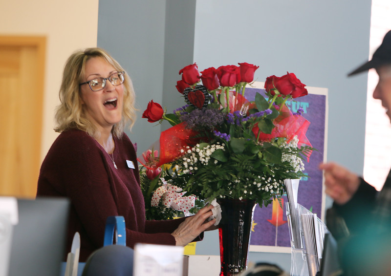 Cheryl Salem of Dracut, head of circulation at Parker Memorial Library in Dracut, chats with library patron Walter Christmas of Dracut, right, as she takes flowers sent by her husband for her birthday back to her office. (SUN/Julia Malakie)