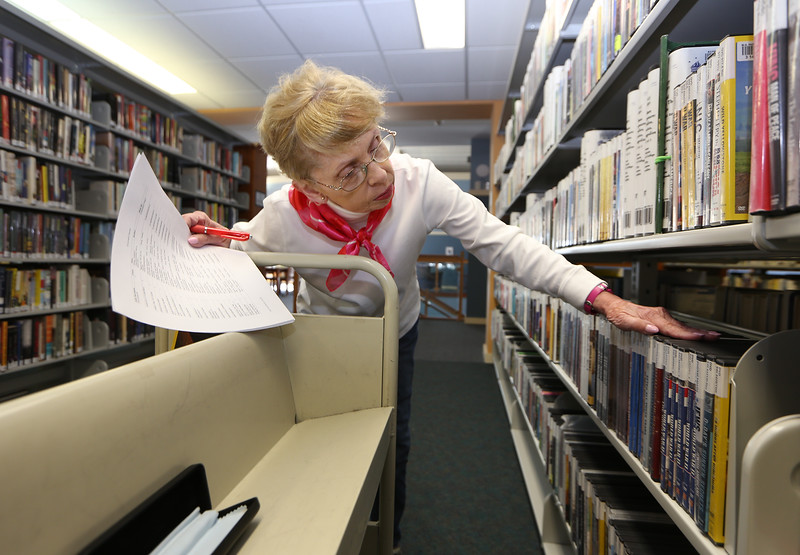 Georgia Cirillo of Dracut, volunteer at the Parker Memorial Library in Dracut, volunteers one day a week, pulling items for interlibrary requests. (SUN/Julia Malakie)