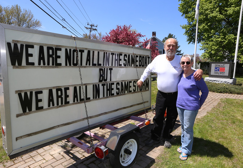 David Paquin and his partner Cathy Kope of Dracut, and the message board sign they've been updating about once a week at Tercentennial Park during the COVID-19 pandemic. Usually they update it 35-40 times a year for upcoming events. (SUN/Julia Malakie)