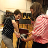 Richardson Middle School music teacher Robin Mallory, who is retiring from Dracut Public Schools at the end of this school year, helps 8th grader Ashleigh Santos remove the name tag from a rented violin case with violin that she was returning.   (SUN/Julia Malakie)