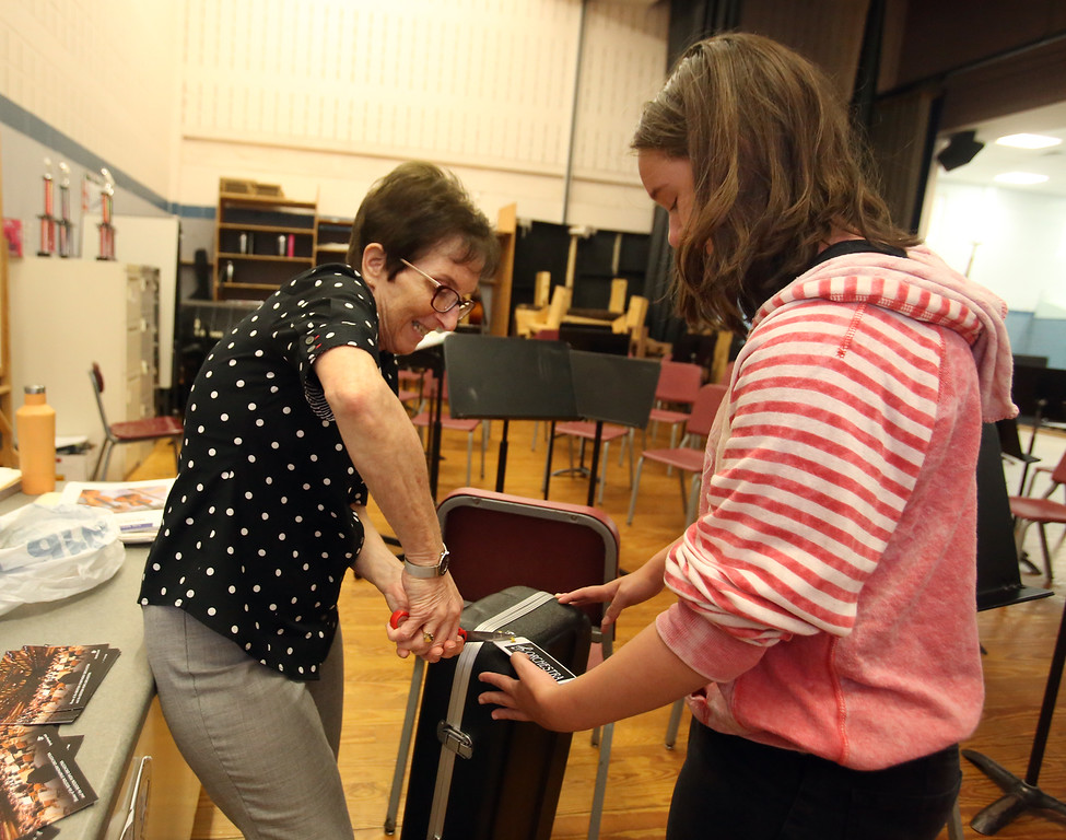 . Richardson Middle School music teacher Robin Mallory, who is retiring from Dracut Public Schools at the end of this school year, helps 8th grader Ashleigh Santos remove the name tag from a rented violin case with violin that she was returning.   (SUN/Julia Malakie)
