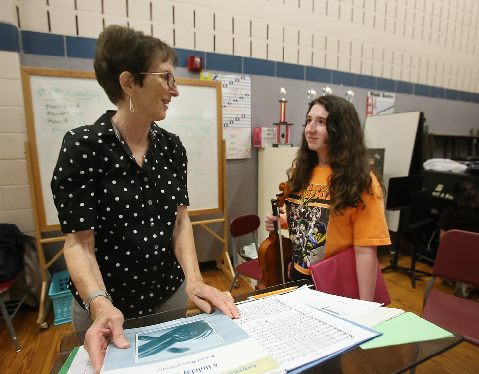 . Richardson Middle School music teacher Robin Mallory, who is retiring from Dracut Public Schools at the end of this school year, talks to 8th grade viola player Irina Martin after their last string orchestra class of the year. (SUN/Julia Malakie)
