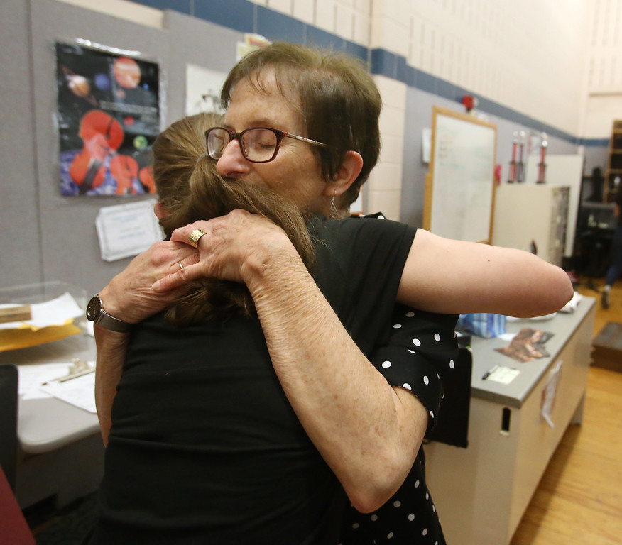 . Richardson Middle School music teacher Robin Mallory, who is retiring from Dracut Public Schools at the end of this school year, hugs 8th grader Alyson Archambault after their last string orchestra class of the year. (SUN/Julia Malakie)