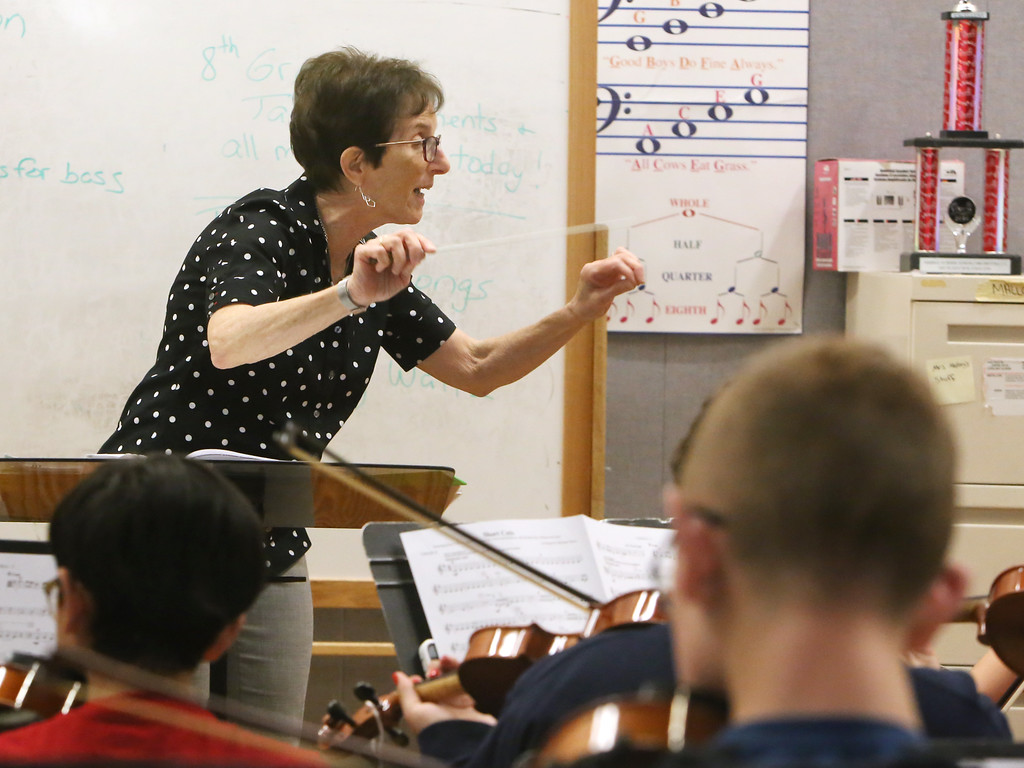 . Richardson Middle School music teacher Robin Mallory, who is retiring from Dracut Public Schools at the end of this school year, conducts the 7th and 8th grade string orcherstra in its last last of the school year.  (SUN/Julia Malakie)