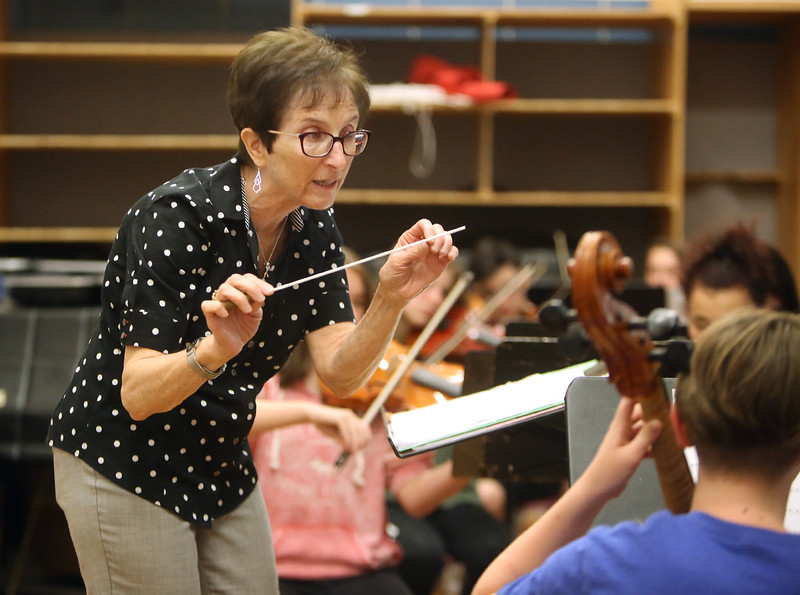 Richardson Middle School music teacher Robin Mallory, who is retiring from Dracut Public Schools at the end of this school year, conducts the 7th and 8th grade string orcherstra in its last last of the school year.  (SUN/Julia Malakie)