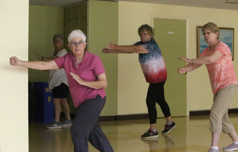 Lunch, card games and tai chi at the Dracut Council on Aging, which will be preparing seniors for the 2020 U.S. Census. Clockwise from front left, Jeanne Roy, Mary Desmarais (rear), Julie Robarge and Jody Lyons, all of Dracut, in beginner's tai chi class. (SUN/Julia Malakie)
