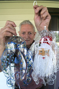 Pat and Earl Baker turn two-liter pop bottles into cool ornaments.This is Earl with just a bird ornament and a Santa ornament.  photo by CHuck Humel