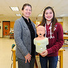 Overlook Middle School Family Health Instructor Laurie Lenart stands with 7th-grader Emily Goodall, 12, Thursday, who saved the life of her 7-year-old sister Cassidy Goodall using the Heimlich this week. Goodall holds a choking child mannequin which she learned to do back blows and abdominal thrusts on, taught by Lenart.<br /> SENTINEL & ENTERPRISE / BRETT CRAWFORD