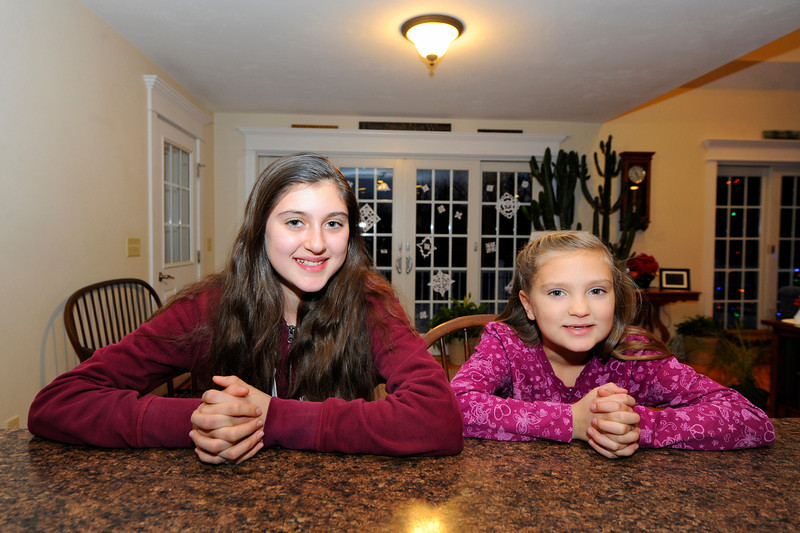 Emily Goodall, 12, (left) sits with her sister Cassidy Goodall, 7, who she saved from choking by using the Heimlich recently, Friday at their Westminster home.<br /> SENTINEL & ENTERPRISE / BRETT CRAWFORD