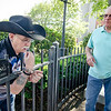 Phil Cebula assists as retired escape artist Roger Lavoie locks himself onto a fence into downtown Fitchburg. SENTINEL & ENTERPRISE / Ashley Green