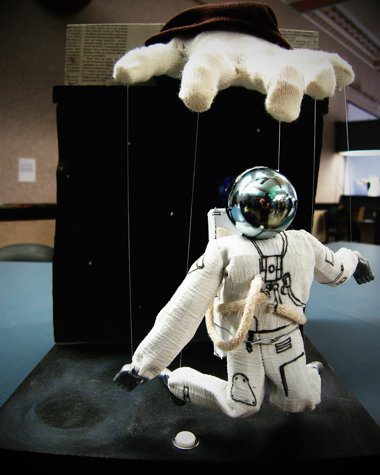 An astronaut dangling puppetlike from the fingers of a bureaucrat.  Press the button on the base and it will dance for your enjoyment, or perhaps to distract you from the current dearth of space-based innovation.