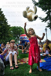 Megan Leschinsky, 4, throws her stuffed bear in the air, while her mom Sarah, left, watches during the Teddy Bear Band's performance for dozens of families Wednesday, July 21, 2010 at the Depot in Wayzata, Minn.
