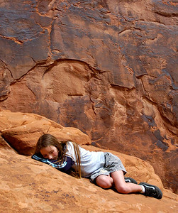 Resting on rock warmed by the midday sun in Arches National park, Utah.