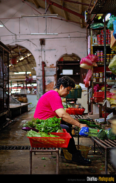 The market is pretty much close and auntie is clearing up whatever vegetables that she have in her stall.