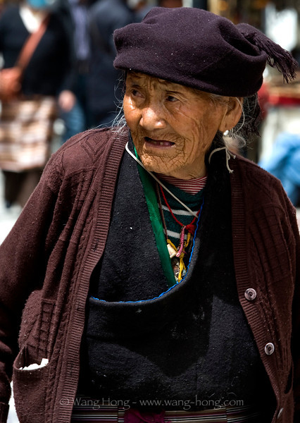 Old Tibetan woman walking in Barkhor Square outside Jokhong Temple in Lhasa