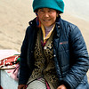 Tibetan woman offering her yak for photograph at side of Yandromtso Lake