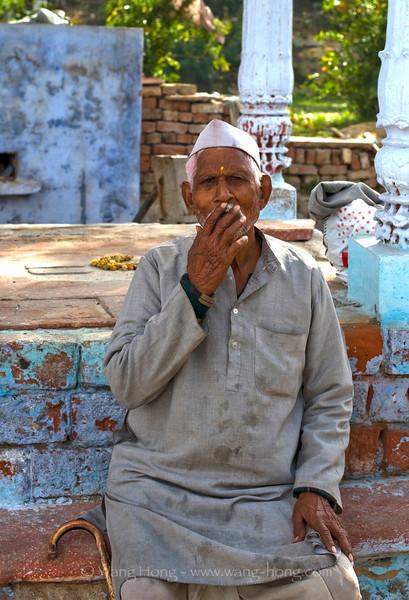 Old Indian man smoking by Yamuna River behind Taj Mahal, India