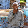Old Indian man smoking by Yamuna River behind Taj Mahal, India