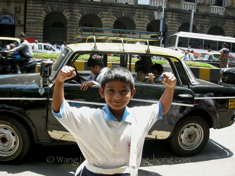 Little Indian boy showing off his mighty arms on the street of Mumbai, India