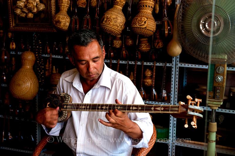 Man playing Rawap in a music instrument shop in Kashgar, summer 2012.