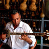 Man playing Rawap in a music instrument shop in Kashgar, summer 2012.