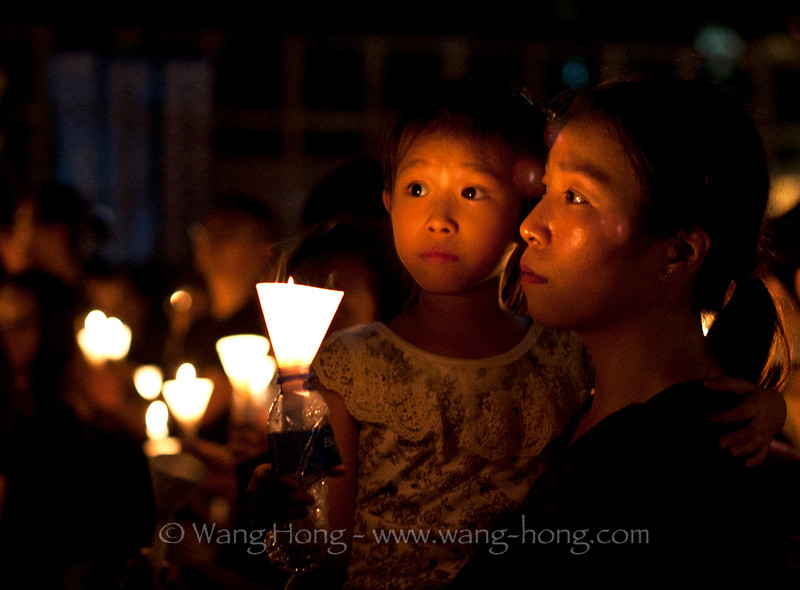 Mom and Child at the candle lit vigil in remembrance of Tian'anmen movement in 1989, Victoria Park, Hong Kong on June 4, 2014.