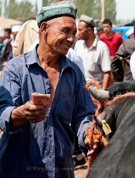 Man with his cash after a transaction at Kashgar Livestock Market, Xinjiang, summer 2012.