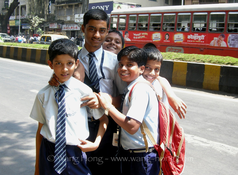 Indian boys getting off school at noon on street of Mumbai, India
