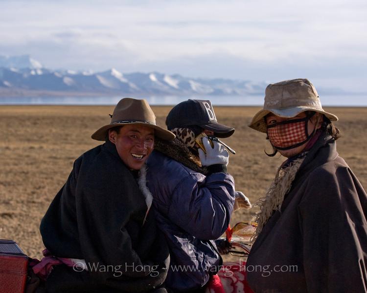 Tibetan men on motorbike by Namtso Lake