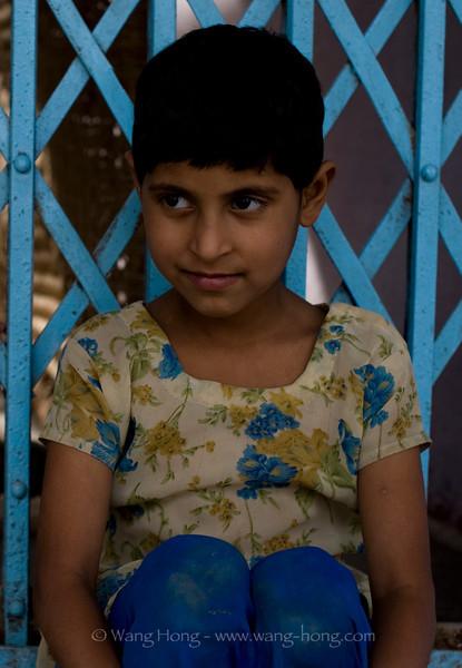 Quite girl sitting by her door in Agra Village, India