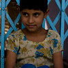 Quite girl sitting by her door in Agra Village, India