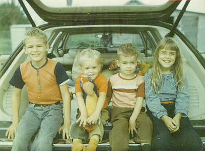My siblings and I sitting in the back of a station wagon (siblings)