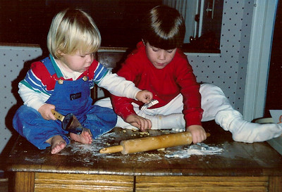 "12.27.13 = Flashback Friday - Holiday Tradition?   A couple of weeks ago I posted a photo of myself, on top of the table rolling cookie dough and then I found this one; a photo of my two nephews keeping the tradition alive! Although I love seeing Kevin's little toes, I hope no one actually ate these cookies!  ""Pleasant memories are the only Eden from which we cannot be driven.""  Fr. Louis Guntzelman"